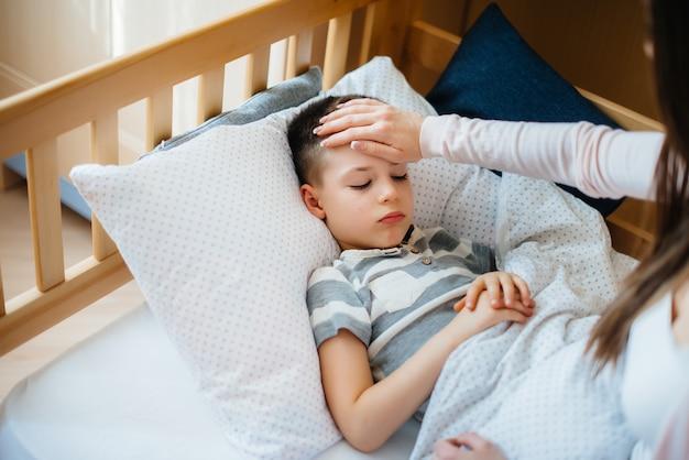 発熱のある子供を母親が面倒を見る。病気とヘルスケア。