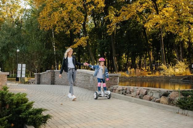 母親は幼い娘に日没時に公園でセグウェイに乗るように教えています。幸せな家族の休暇。