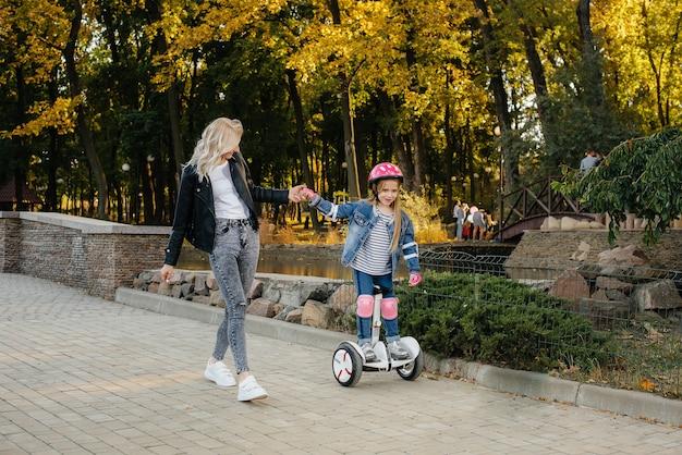 Мать учит свою маленькую дочь кататься на сегвее в парке на закате. счастливый семейный отдых.