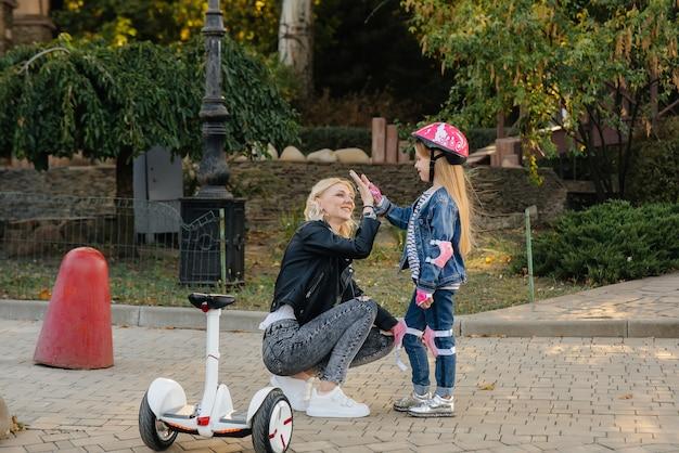 어머니가 어린 딸에게 일몰 동안 공원에서 세그웨이를 타도록 가르치고 있습니다.