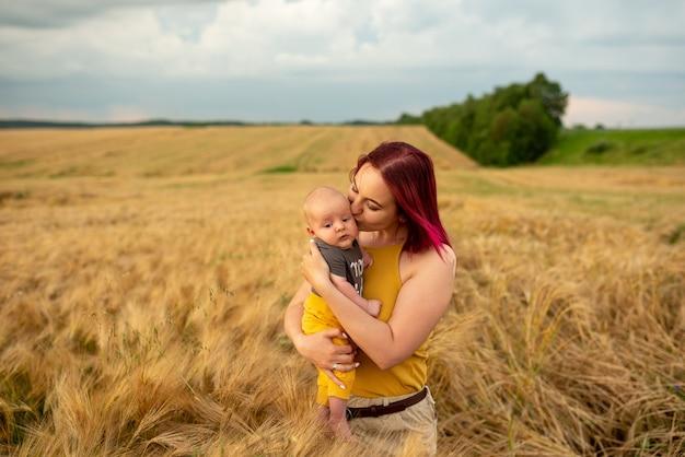 Мать нежно держит на руках своего трехмесячного сына на пшеничном поле.