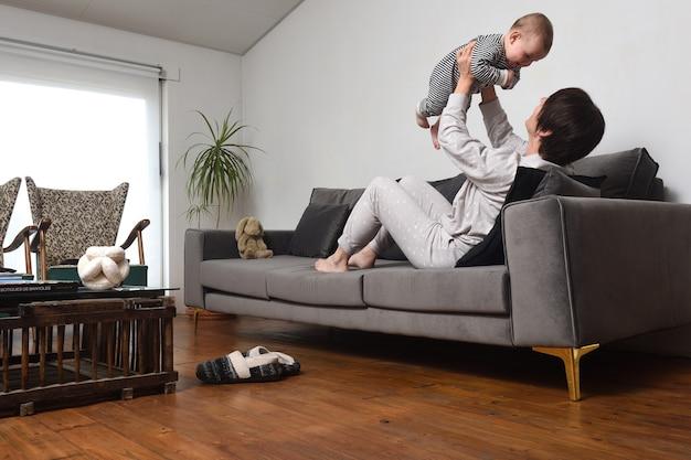 自宅のソファで赤ちゃんと遊んでいるお母さんパジャマを着ているお母さん