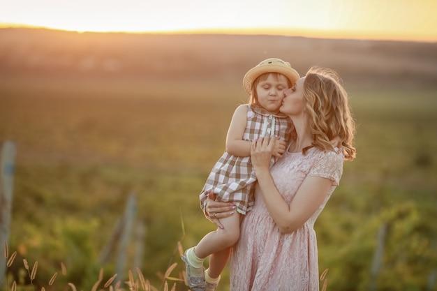 赤ちゃんを抱きしめる母親が夕暮れ時に畑に背を高くして赤ちゃんを抱きしめる