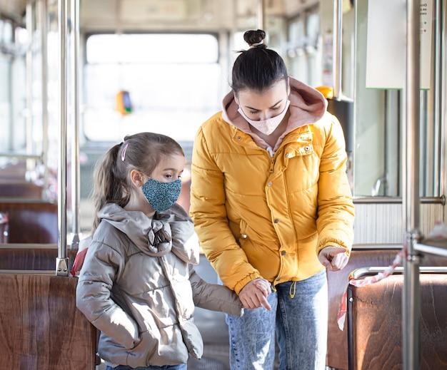 パンデミックの最中にマスクを着用し、空の公共交通機関に子供を連れた母親。コロナウイルス。