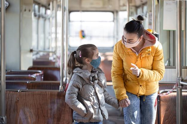 Мать с ребенком в пустом общественном транспорте в масках во время пандемии коронавируса