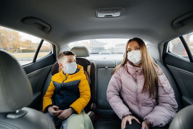 病院に行くマスクをした車の後部座席に子供がいる母親。伝染病、検疫