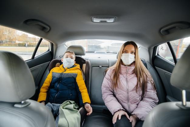 Мать с ребенком на заднем сиденье автомобиля в масках едет в больницу. эпидемия, карантин.