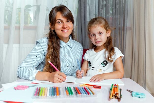 子供を持つ母親がテーブルに座って宿題をします。子供は家で学びます。ホームスクーリング。