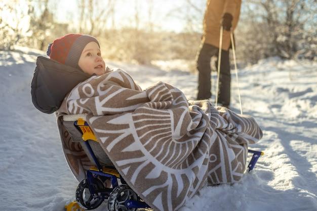 晴れた日の凍るような冬の朝、子供を持つ母親が歩く