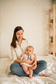 작은 딸과 함께 어머니가 방의 침대에 흰 담요에 앉아있다.