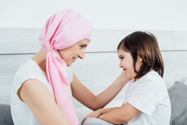 ピンクのスカーフを身に着けている癌の母親は、子供を優しくそして幸せに愛撫します。彼らは白い背景のベッドに座っています