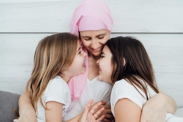 がんの母親はピンクのスカーフを身に着け、金髪と茶色の髪の2人の娘を優しく幸せに抱きしめています。