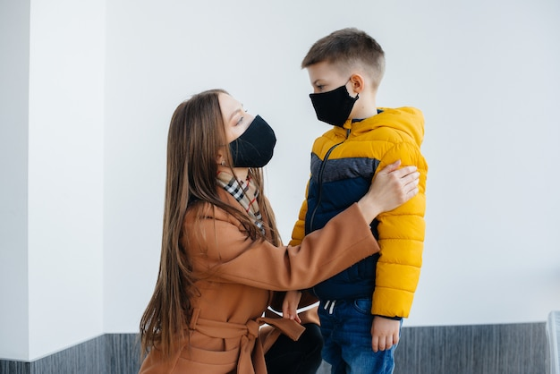 Мать с ребенком стоит в маске во время карантина. пандемия, коронавирус.