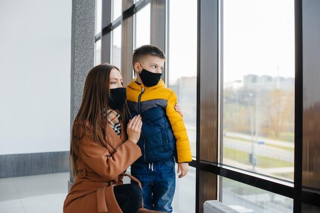 検疫中に子供を持つ母親がマスクに立っている