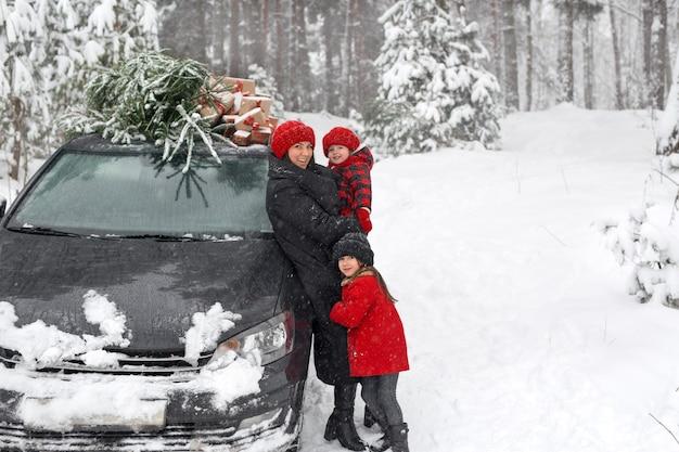 市場からのクリスマスツリーの横に娘を持つ母親