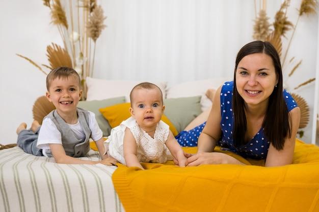 Мать с сыном и дочерью лежит на кровати в спальне и улыбается в камеру.