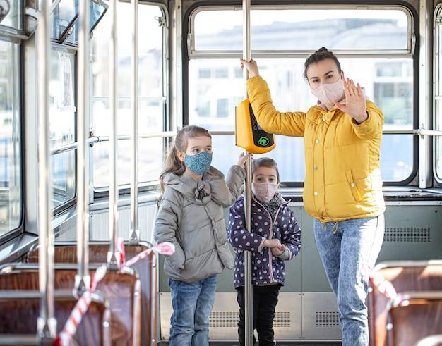 Мама с маленькими детьми в масках защищает себя от коронавируса в общественном транспорте.