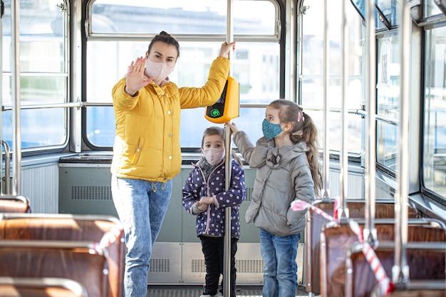 マスクを着用した公共交通機関に2人の子供を持つ母親。パンデミックの間。コロナウイルス。