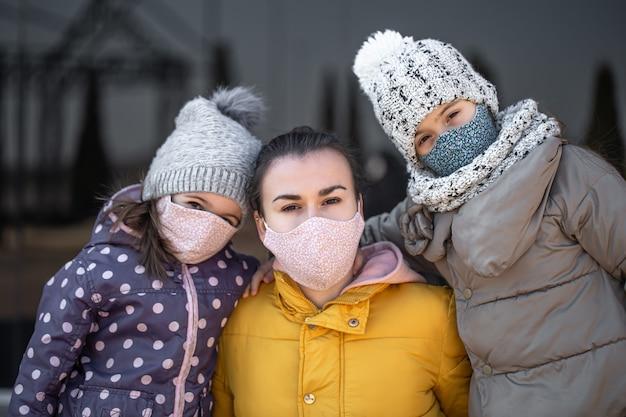 대유행 코로나 바이러스 동안 마스크를 쓴 두 딸을 둔 어머니.