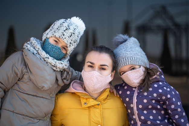 Мать с двумя дочерьми в масках во время пандемии коронавируса.