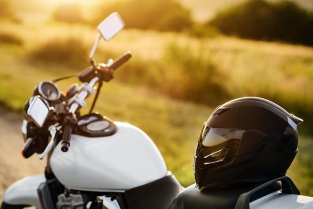 Мотоциклетный шлем лежит на сиденье мотоцикла в лучах заходящего солнца.