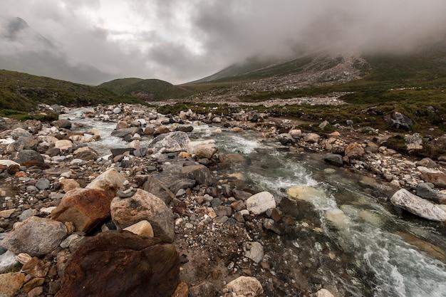 Горная река с множеством разных камней в тумане. склон горы с камнями. по горизонтали.