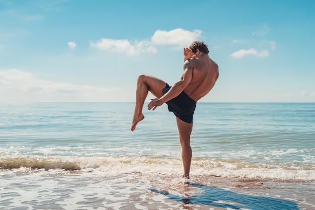 Тренировка по тайскому боксу или кикбоксеру с теневым боксом на открытом воздухе на берегу моря.