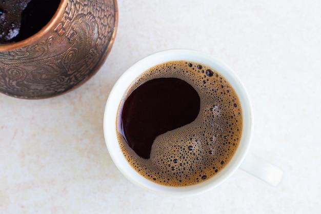 ライトテーブルの表面に淹れたてのコーヒーを入れたマグカップとトルコの上面図朝の目覚め