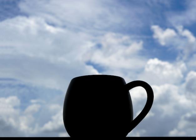 青空の背景に雲とバックライトのコーヒーのマグカップ