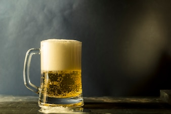 A mug of fresh beer on a dark background of a wooden table.