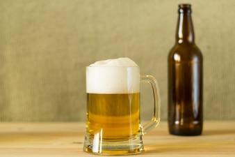 A mug of fresh beer with foam, a bottle.