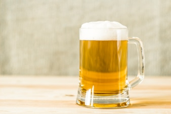 A mug of fresh beer with foam.