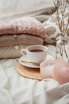 Кружка горячего какао, вязаные кофточки, букет белых сухоцветов в вазе, свеча на кровати. завтрак в постель. уютно. весна.