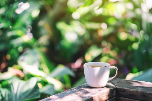 정원의 나무 발코니에서 뜨거운 커피 한 잔