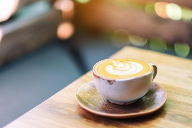 아침에 나무 테이블에 뜨거운 라떼 커피 한 잔