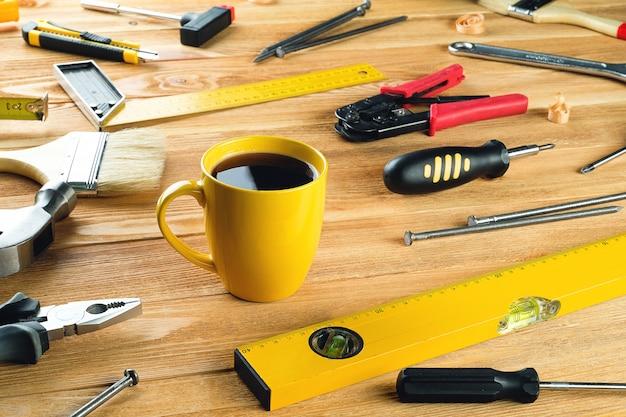 お茶やコーヒーのマグ、木製のテーブルでの専門家の建設や家の修理のための道具