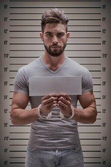 空白の情報カードを持つ囚人のマグショットがクローズアップ