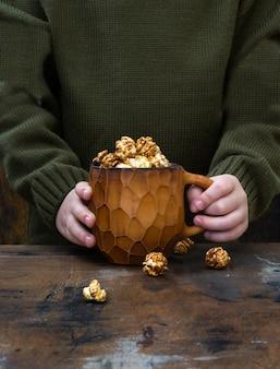 Кружка с теплым напитком какао и попкорном в руках ребенка. осенний уютный дом, теплый свитер