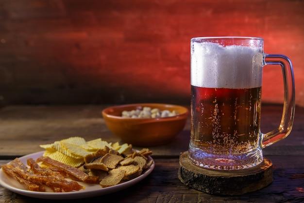 나무 테이블에 칩을 넣은 맥주와 피스타치오가 든 머그