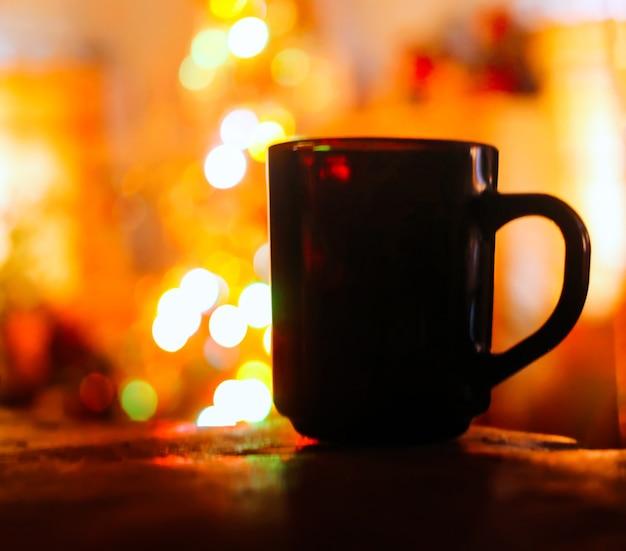 カラフルなクリスマスの飾りに熱いお茶が入ったマグカップがクローズアップ。