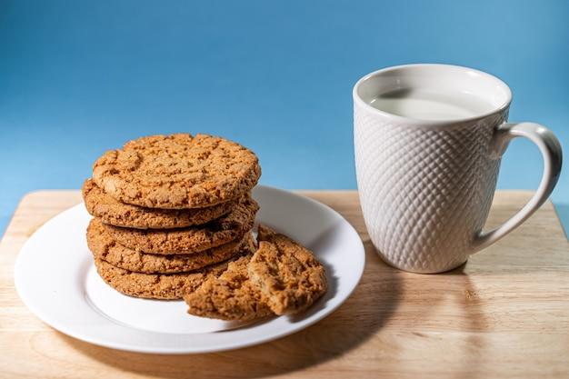 木製のテーブルの白いプレートにミルクとオートミールのクッキーが入ったマグカップと、blに新鮮なオートミールのクッキーが入ったマグカップ...