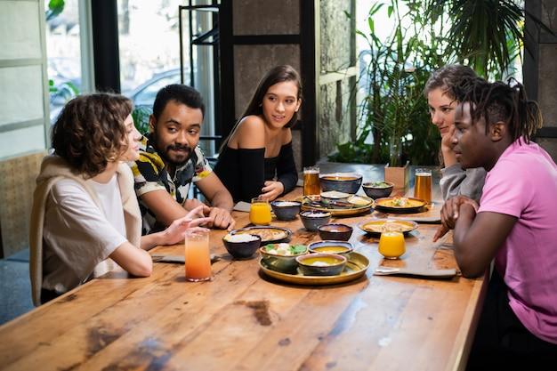 Многонациональная группа друзей, хорошо проводящих время в кафе