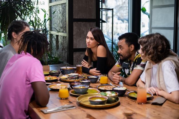 Многокультурная группа молодых людей в кафе, едят азиатскую еду, пьют коктейли, общаются в чате