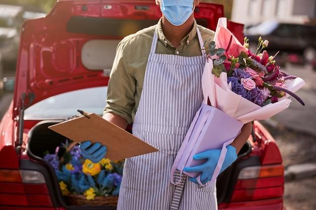 펜 클립 보드와 차 옆에 포장 된 꽃다발을 들고 다민족 플로리스트