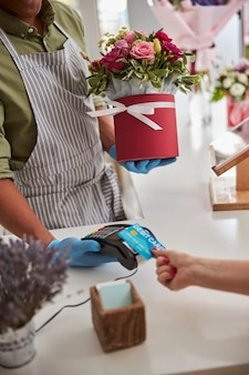 클라이언트 직불 카드에서 지불을 인출하는 동안 장미 다발로 서있는 다민족 남성 플로리스트