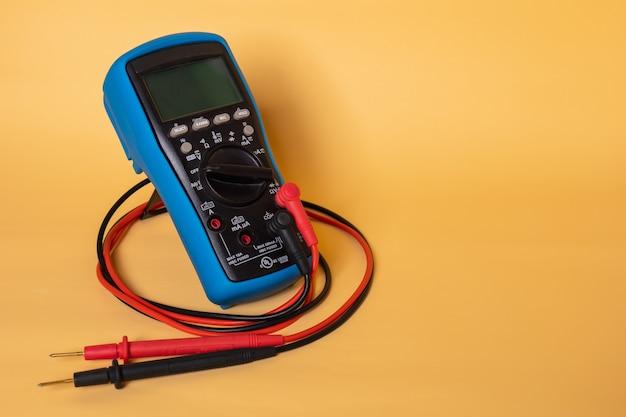 電圧、抵抗、電流、温度などのさまざまな値を測定するために使用されるマルチメータ。現場にあります。 Premium写真