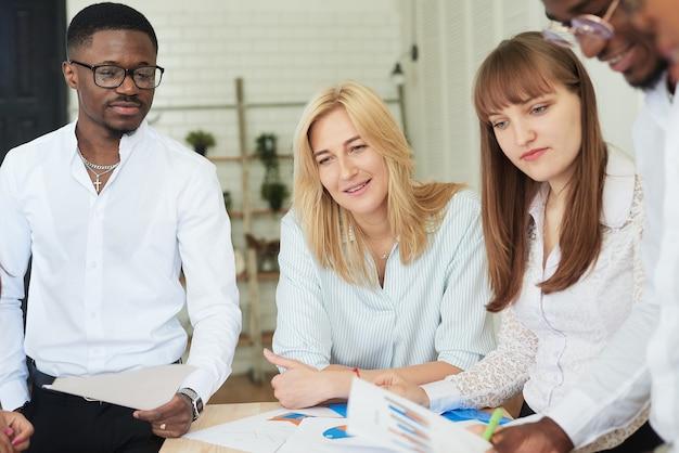 다국적 긍정적인 사람들의 회사는 사무실에서 일하고 작업 서류를 살펴봅니다.