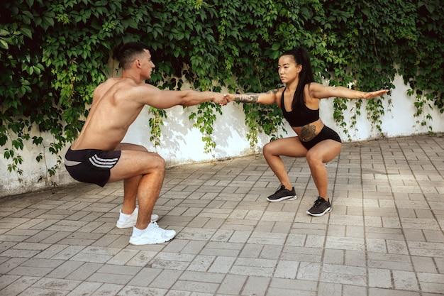 Мускулистые спортсмены на тренировке в парке. гимнастика, тренировки, гибкость фитнес-тренировок. летний город в солнечный день на поле фона. активный и здоровый образ жизни, молодость, бодибилдинг.