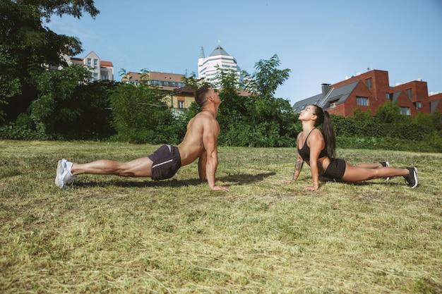 公園で運動をしている筋肉の運動選手。体操、トレーニング、フィットネストレーニングの柔軟性。宇宙フィールドで晴れた日の夏の街