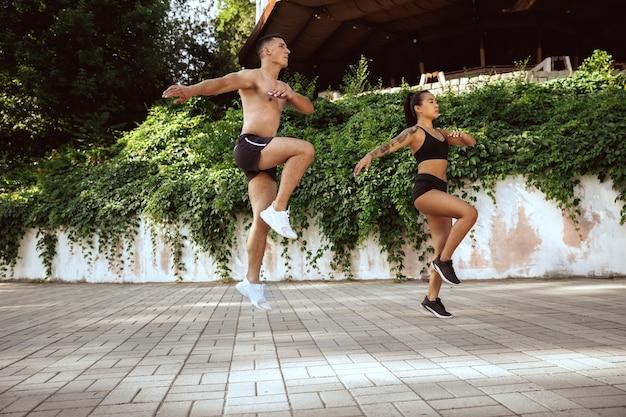Мускулистые спортсмены на тренировке в парке. гимнастика, тренировки, гибкость фитнес-тренировок.